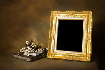 golden vintage frame on wooden table over gold background