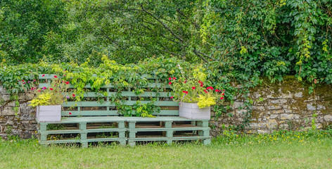 Feneyrols, Midi Pyrenees, France - July 23, 2017: Lonely sitting bench in green color decorated with flowers in a garden