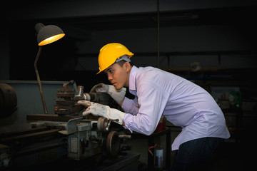 Asian engineer man wearing safety helmet checking and using an equipment in the laboratory. concept of manufacturing mechanical workshop measurement and tools.