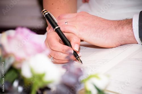 bride groom signing wedding register documents focus on hand