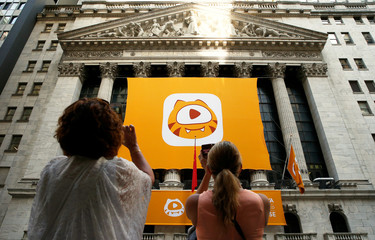 People take pictures of the Huya Inc. logo ahead of the company's IPO at the New York Stock Exchange (NYSE) in New York