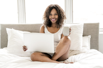 Beautiful black woman on a white bed with laptop and coffee
