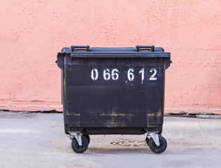 garbage container on a pink wall background