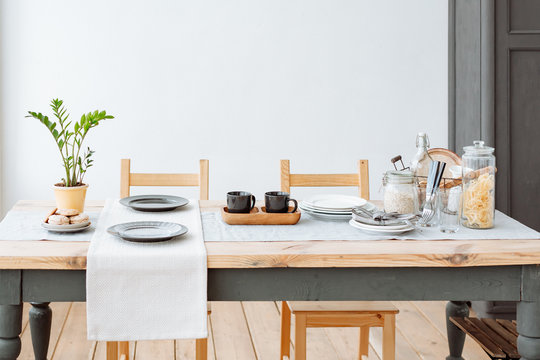 Canteen. wooden dining table with crockery and Cutlery. Light natural interior. Home comfort.