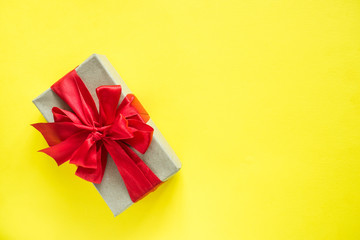 Gift box with red ribbon bow on bright yellow background Copy space for text