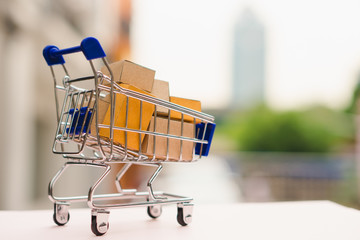 Mini shopping cart contain paper box using as e-commerce, online shopping and business marketing concept