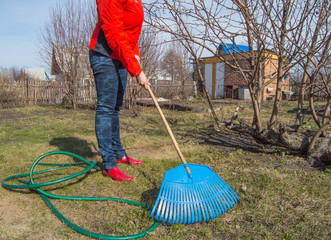 Young woman farmer working in the garden, rake clears the lawn, garden tools