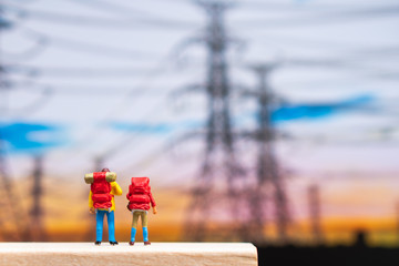 Miniature people, couple backpacker standing in front of electric pole using as travel and exploring concept