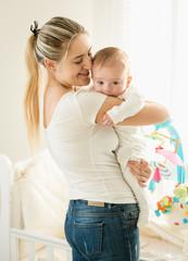 Portrait of happy smiling mother hugging her baby in bedroom at cot
