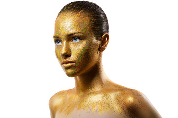 young girl in gold paint. the particles of metal powder on her face.