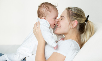 Closeup portrait of 3 months old baby boy and smiling mother having fun on bed