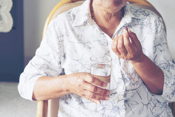 Asian elderly woman are taking and eating medicines and vitamins for help sick and healthy..