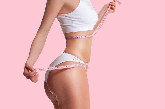 Woman measuring her sporty body, successful weight loss