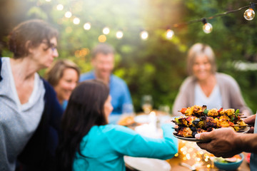 group of friends in their forties gathered around a table in the garden to share a bbq meal. A man offers chicken skewers to guests
