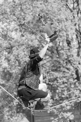 black and white photograph of Street performer walking tight rope and playing violin tree in background