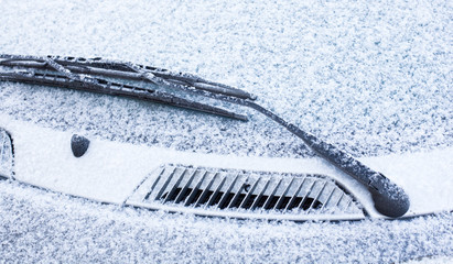 Car wipers and windscreen covered with snow