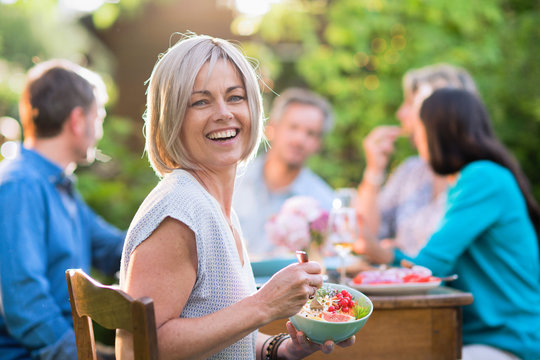 Looking at the camera a beautiful woman in her forties with a bowl of mixed salad by hand. She sits around a table in a garden with friends for dinner.