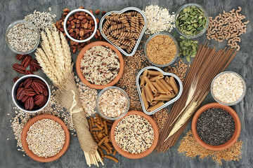 High fibre healthy food concept with fresh whole wheat pasta, cereals, grains, seeds, nuts and wheat sheaths. Foods high in omega 3, antioxidants and vitamins. Rustic background on marble, top view.