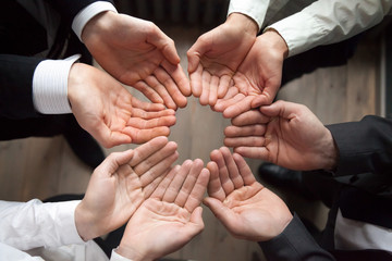 Team people join hands in circle palms up as concept of care protection, contribution in growing business and startup growth, enganing crowdfunding, unity, trust or safety concept, close up top view