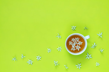 Cup of tea with white flowers on bright green surface.