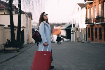 female traveler walks the city with a red suitcase.