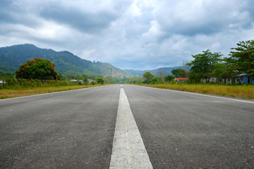straight asphalt road in rural landscape - empty runway