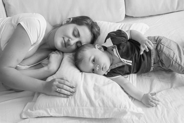 Black and white high point view photo of young mother sleeping next her baby boy lying in bed