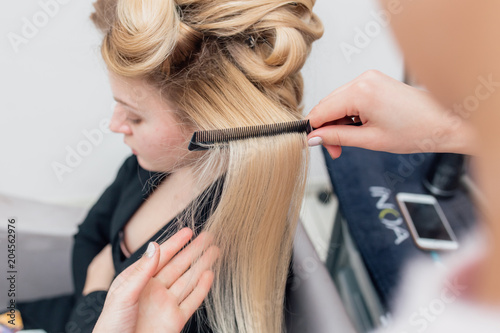 Hairdressers Hands Drying Long Blond Hair With Blow Dryer And Round