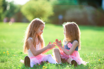 Adorable little girls on spring day outdoors sitting on the grass