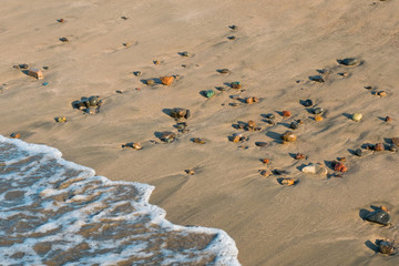 wave hits beach with colorful pebble stones