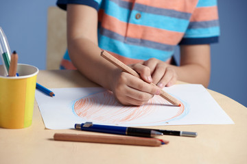 Boy drawing with colorful pencils. Close view.