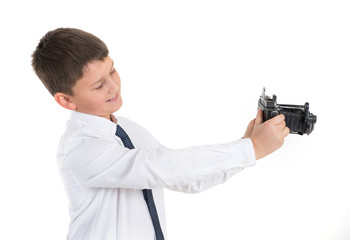 Glad child, teenager with a photocamera in a hand on the white isolated background. A child takes pictures.