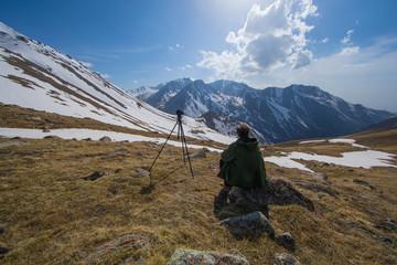 photographer traveler takes a mountain landscape,a camera on a tripod