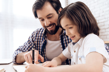 Bearded father helps young son to do school homework.