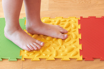 A child steps on an orthopedic mat.