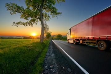 Fotobehang - Truck driving on the asphalt road between trees in a rural landscape at sunset