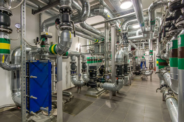 Modern independent heating system in boiler room. Pipelines, water pump, valves, heat exchanger.