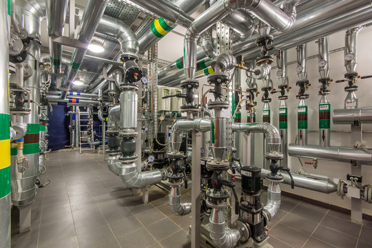 Central heating system in the basement of an large building. Pipelines, water pump, valves, manometers