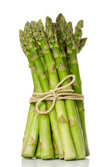 Bundle of fresh green asparagus shoots, upright standing. Sparrow grass. Cultivated Asparagus officinalis. Spring vegetable with thick stems and closed buds. Food photo close up front view over white.