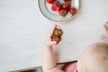 Hand of a child with a strawberry on a rustic background, a plate of strawberries.