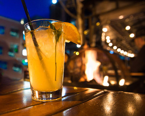 Refreshing cocktail beverage with ice and straw scene from outdoor restaurant at night with lights and firepit.