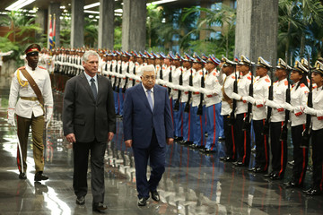 Cuban President Miguel Diaz-Canel and Palestinian President Mahmoud Abbas review an honour guard during a ceremony at the Revolution Palace in Havana