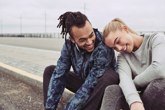 Smiling young couple taking a break from an outdoor run