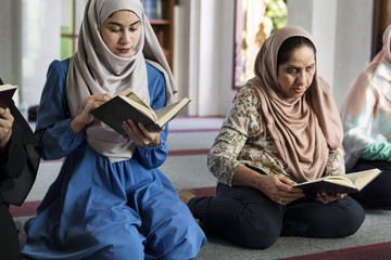 Muslim women reading Quran in the mosque during the Ramadan