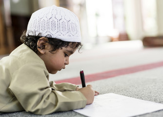 Little boy playfully drawing in a mosque during Ramadan