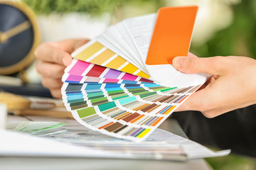 Female designer working with color palette samples at table