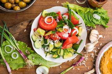 Fresh vegetables Greek salad with tomatoes, cucumbers, onion slices and sprouts. Served with olive oil. Raw vegan vegetarian healthy food