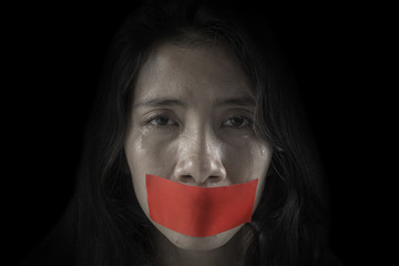 Unhappy woman with her mouth covered by tape