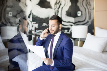 Successful broker or financier in suit reading terms of new financial contract to business partner by smartphone while sitting on bed in hotel room