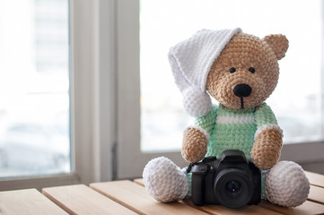 Teddy bear with camera on wood table. Copy space. Selective focus